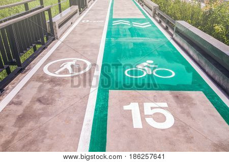 Walk and bike lane with speed limit. Signs for bicycle and walking painted on the concrete lane for exercise