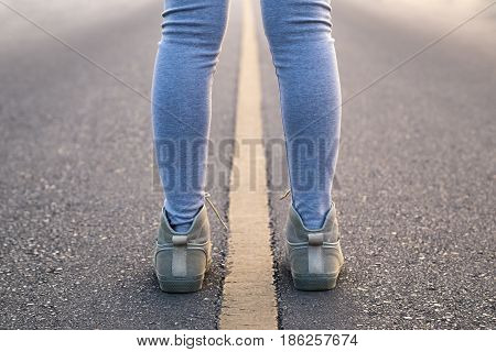 A woman with pair of legs stand astride line road for a exercise in the morning.