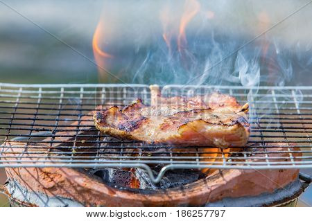 grill pork neck on stove with flame