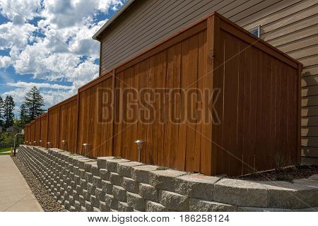 Wood fence cement stack stone blocks retaining wall and landscaping lighting