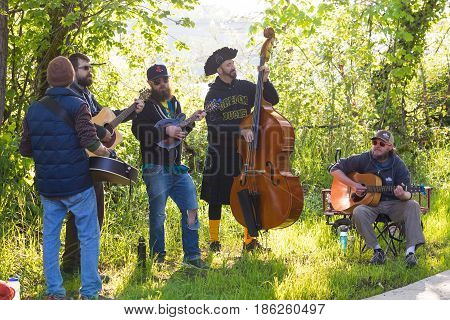 EUGENE, OR - MAY 7, 2017: Bluegrass band perfoms along the river path during the 2017 Eugene Marathon race held on the University of Oregon campus.