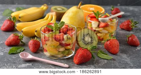 Fruit salad with strawberries on a gray background