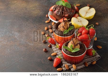 Baked pear in chocolate on a brown background