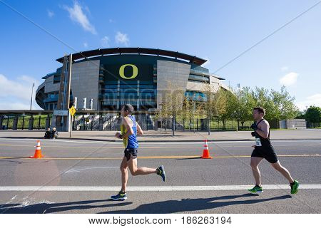 EUGENE, OR - MAY 7, 2017: Runners race in front of Autzen Stadium at mile 16 of the 2017 Eugene Marathon race held on the University of Oregon campus.