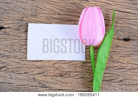 Close yp of purple tulips and blank card on wooden.