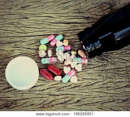 Assorted pills pills for health care on wooden background.