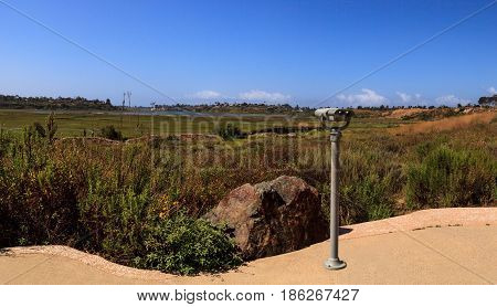 Telescope viewer pointed at the Upper Newport Bay Nature Preserve hiking trail winds along the marsh where you will see wildlife in Newport Beach California USA