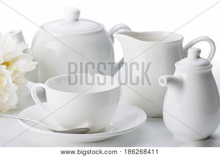 China tea set: cup with saucer and spoon, teapot, milk jug close-up isolated on white background