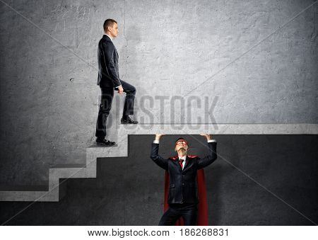 A businessman in a red cape holding a concrete floor and stairs for another businessman to step on. Business and success. Cooperation. Unexpected help.