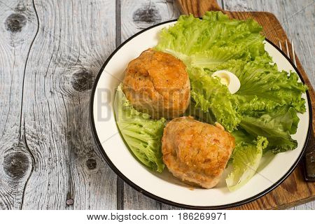 Chicken souffle and leaves of fresh green salad on a white plate on a gray wooden background.