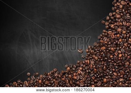 Group of roasted coffee beans on an empty blackboard with copy space