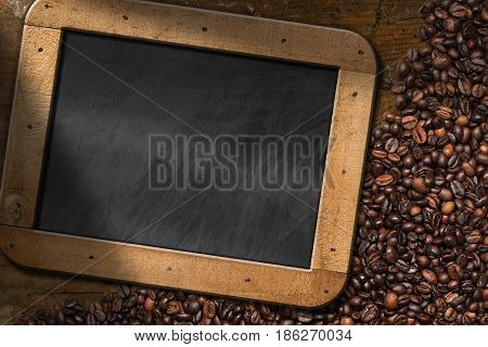 Roasted coffee beans with an empty blackboard with wooden frame and copy space