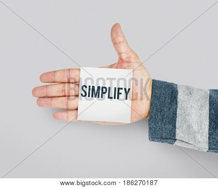 Hand with Sticky Note Showing Simplify Word