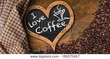 I Love Coffee - Blackboard in the shape of a heart with roasted coffee beans and a coffee cup. On a wood background with a checkered tablecloth