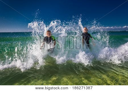 Two boys swimming and playing with large ocean waves