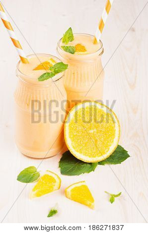Freshly blended orange citrus smoothie in glass jars with straw mint leaf cut orange close up. White wooden board background.
