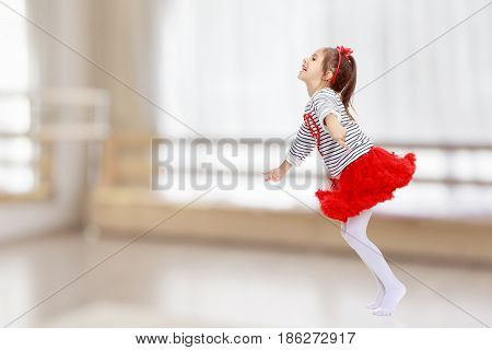 Little girl in a red skirt and bow on her head.She jumps waving her arms.In the room with the big bright window in the wall.