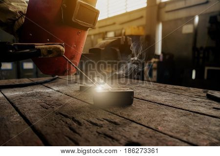 Inverted welding machine welding equipment on a wooden desk with workshop background welding mask leather gloves electrodes high-voltage wires with clips set of accessories for arc welding