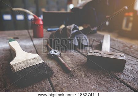 Inverted welding machinewelding equipment on a wooden desk with workshop backgroundwelding maskleather gloveswelding electrodeshigh-voltage wires with clipsset of accessories for arc welding.