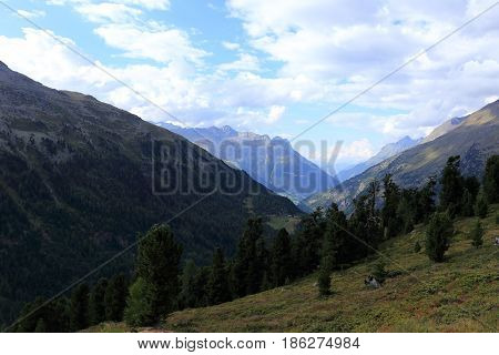 peaks in the alps with clouds on sky