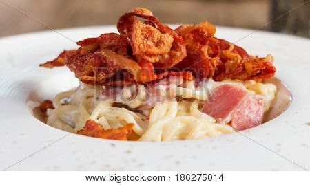 closeup juicy carbonara with ham and bacon on top in white plate
