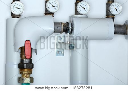 some pipes and thermometers in a heating room