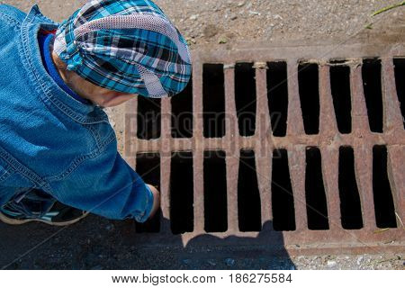 A small boy dropped a toy in a street drain and tries to get it on his own