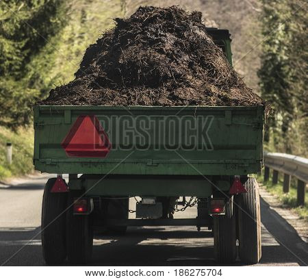 Tractor trailer loaded with natural fertilizer on a trailer.