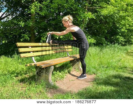 Muscular Sporty Woman Limbering Up In A Park