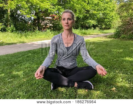 Young Woman Meditating Outdoors On Grass