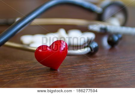 Medical Stethoscope And A Red Heart With A Syringe And Pills On A Wooden Table