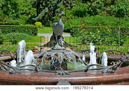 A beautiful and magnificent fountain is framed by an iron bird. The fountain is located on the territory of the Russian Kremlin in the center of the capital city