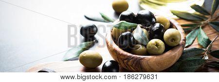 Fresh olives. Black and green olives in wooden olive bowl. Long banner format.