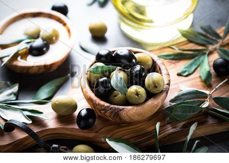Fresh olives and olive oil. Black and green olives in wooden olive bowl.