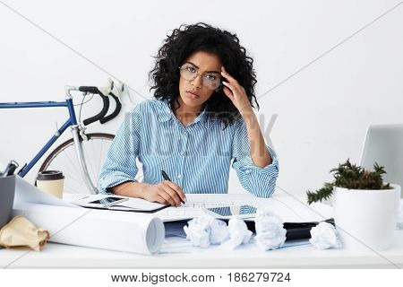 Frustrated Businesswoman Dressed Formally Holding Pen, Making Notes In Sketchbook, Suffering From La