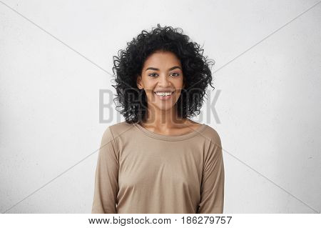 Waist Up Portrait Of Cheerful Young Mixed Race Female With Curly Hair Posing In Studio With Happy Sm