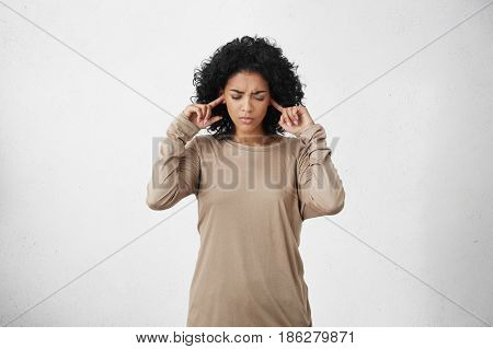 Stressed Frustrated Young Dark-skinned Woman Wearing Beige Long-sleeved Top Plugging Her Ears With F