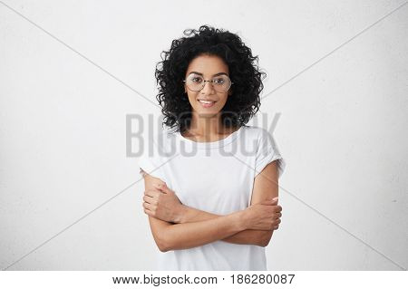 Body Language. Isolated Studio Portrait Of Constrained Young Dark-skinned Woman In Round Eyewear Sta