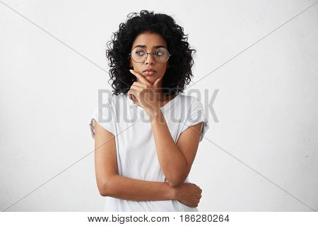 Portrait Of Beautiful Casually Dressed Young Woman In Round Glasses Having Doubtful Expression, Look