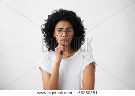 Indoor Shot Of Beautiful Thoughtful Young Mixed Race Housewife Staring At Camera With Thoughtful Loo