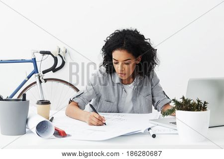 Focused Young Woman Engineer With Curly Hair Busy Making Drawings, Using Pencil. Hardworking Female