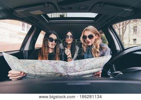 View Of Three Beautiful Young Cheerful Women Looking Into The Map While Sitting In Car