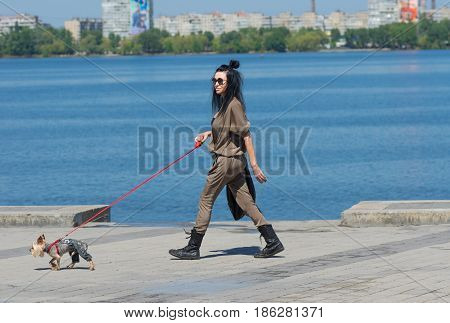 Dnipro Ukraine - May 06 2017: Dandy Yorkshire Terrier dog wearing jeans leads fashionable woman on a Dnepr river embankment in Dnepr city Ukraine