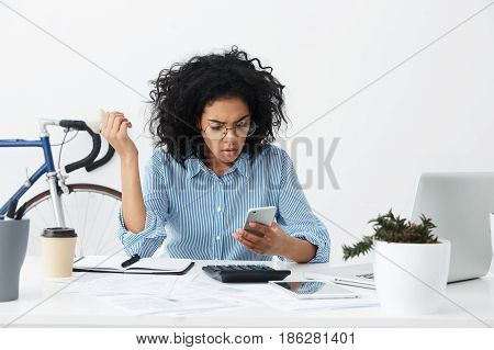 Perplexed Young Woman Employee In Formal Shirt And Round Eyewear Having Frustrated Look While Facing