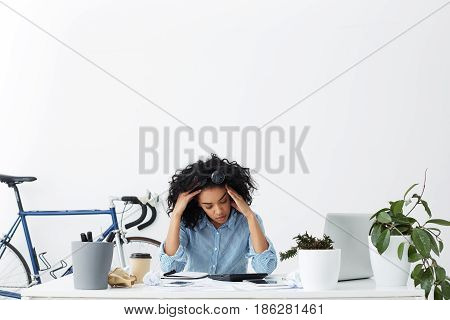 Indoor Portrait Of Tired Overworked Young Businesswoman Feeling Stressed While Facing A Problem, Doi