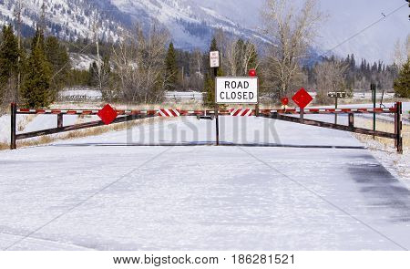 Road Closed Sign And Gate Blocking Road Access During Winter Time
