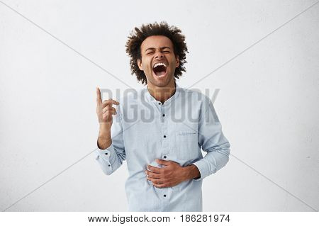 Isolated Studio Shot Of Positive Cheerful Young African American Male With Funky Hair Closing His Ey