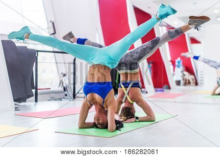 Girls working out together doing wide leg headstand, advanced yoga pose in modern fitness club.