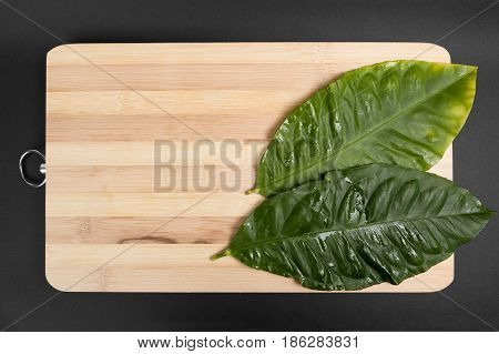 Leaves of lemon lie on the wooden board on a black background