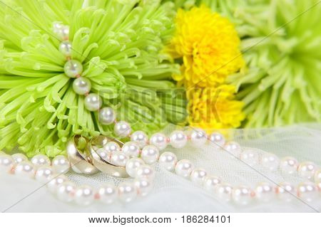 White necklace of pearls wedding rings and bouquet of chrysanthemums on a white veil